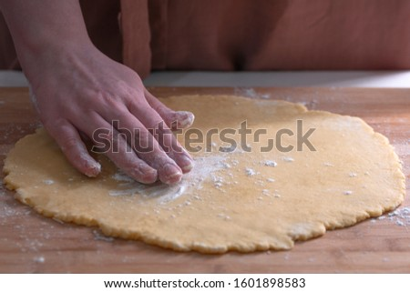 Cut cookies from rolled dough.Cook cuts cookies out of rolled dough. #1601898583