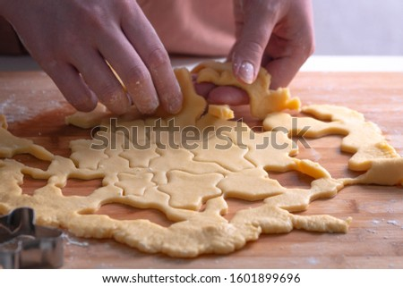 Cut cookies from rolled dough.Cook cuts cookies out of rolled dough. #1601899696