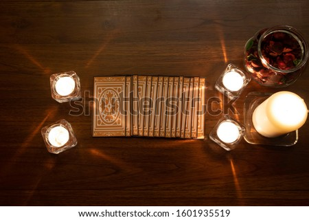 Tarot cards spread on a wooden table with burning candles.Mystic and Forecasting concept.Top view. #1601935519