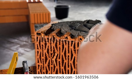 Worker puts cement on a brick on a construction site. Stock footage. Bricklayer laying bricks to make a wall, he is putting grout on top of a brick #1601963506