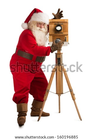 Santa Claus taking picture with old wooden camera. Full length portrait isolated on white background