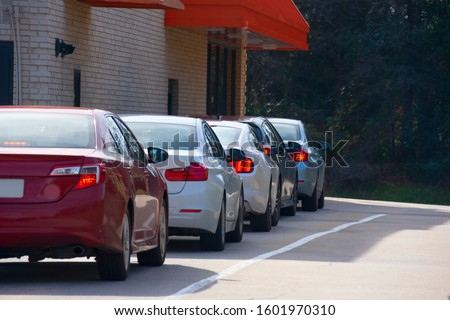 Generic drive thru pickup window with cars waiting in line to get their products or food. Royalty-Free Stock Photo #1601970310