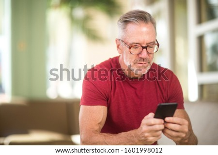Mature man reading and texting on his mobile phone. Royalty-Free Stock Photo #1601998012
