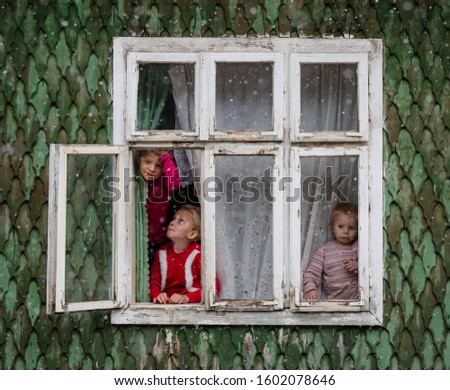 Vama, Romania, December 2019: traditional simple rural wooden house in northern Romania with children playing at the window in winter during snow #1602078646