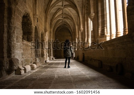 Tourist woman walks through the interior of the cloister of a cathedral with a vintage camera in a Spanish city. Concept: historical tourism, cultural tourism #1602091456