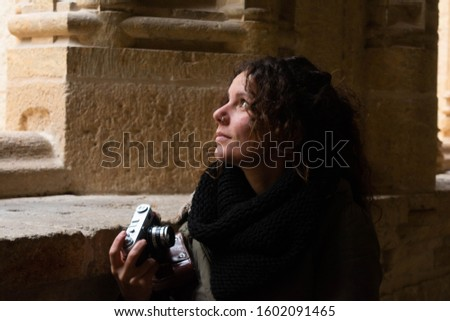 Tourist woman walks through the interior of the cloister of a cathedral with a vintage camera in a Spanish city. Concept: historical tourism, cultural tourism #1602091465
