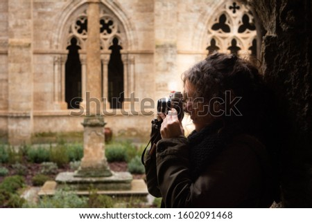 Tourist woman walks through the interior of the cloister of a cathedral with a vintage camera in a Spanish city. Concept: historical tourism, cultural tourism #1602091468