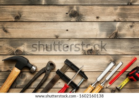 Top view of carpenter work tools on an antique wooden table. Construction industry, do it yourself. Text space. #1602160138
