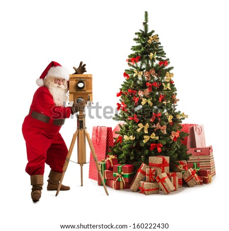 Santa Claus taking picture with old wooden camera standing near Christmas tree. Full length portrait isolated on white background