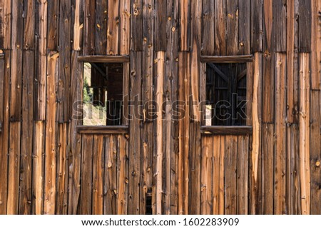 Windows in an old wooden weathered building #1602283909