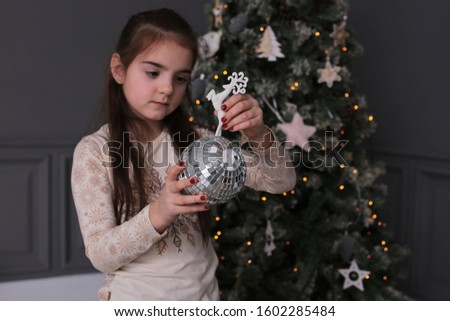 Young beautiful girl with long dark hair is fooling around with cookies on New Year's bokeh lights at a decorated Christmas tree #1602285484
