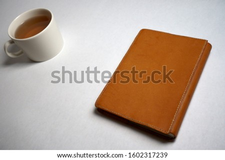 leather book jacket and a cap of tea Royalty-Free Stock Photo #1602317239