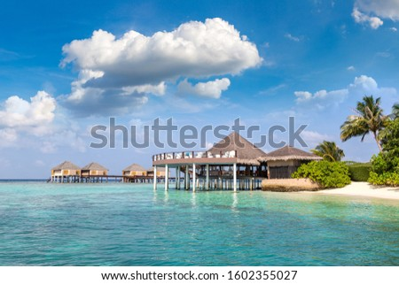 Water Villas (Bungalows) and wooden bridge at Tropical beach in the Maldives at summer day #1602355027