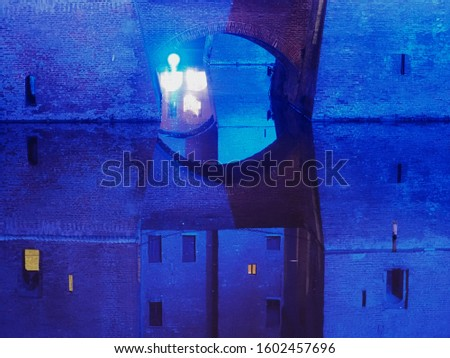 Ferrara, Italy. Este castle illuminated by blue lights to celebrate the Christmas season. The castle is reflected in the waters of the moat. #1602457696