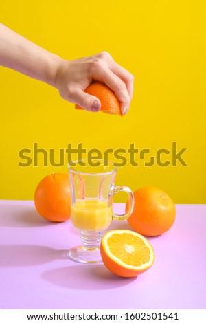 Female hand holding crushes orange and juice. #1602501541