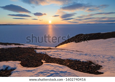 Spring arctic landscape with the midnight sun and the coast of the Arctic Ocean. North of the Arctic Circle at the end of May, the sun does not set at night over the horizon. Pevek, Chukotka, Russia. #1602740416