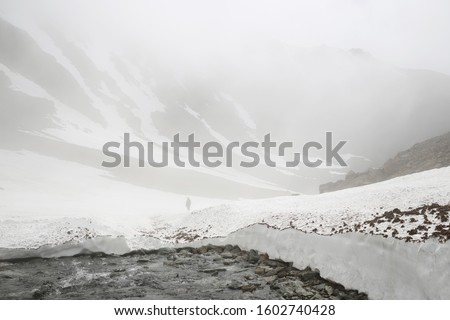 Misty mountain landscape. In the distance, a traveler on a snowy mountain pass. Hiking, trekking and mountain climbing. Golden Ridge, Chukotka, Siberia, Far East of Russia. #1602740428