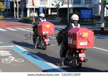 CHIBA, JAPAN - January 1, 2020: A pair of post office delivery workers on motorbikes delivering New Year cards on New Year's Day in Ichikawa City. #1602811849