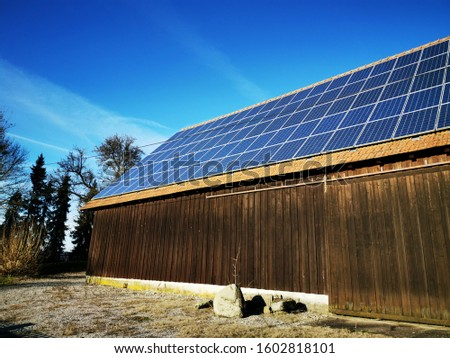 Photovoltaic panels or solar panels on a old wooden barn,with a beautiful blue sky on background,in a small village in the Bavarian south region of Germany ,Europe. #1602818101