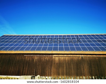 Photovoltaic panels or solar panels on a old wooden barn,with a beautiful blue sky on background,in a small village in the Bavarian south region of Germany ,Europe. #1602818104