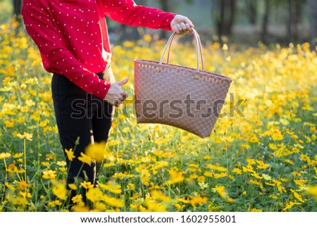 The girl carried the basket through the yellow flower fields during the sunset and shone from behind. Reduce global warming by refraining from using plastic bags. #1602955801