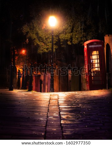 Red telephone box in Bath, somerset at night. Cobbled street lit up by street light #1602977350