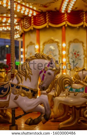 Horses to sit in a street festive carousel. Mass festivities and fun. Close-up. Vertical. #1603000486