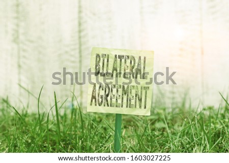 Writing note showing Bilateral Agreement. Business photo showcasing Legal obligations to nonbinding agreements of principle Plain paper attached to stick and placed in the grassy land. #1603027225