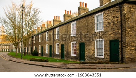 A long curving terrace of C19th workers cottages make up Lower Park Street. Gault brickwork and uniform windows and dark green painted doors - a tranquil street. Open lawned garden to the front #1603043551