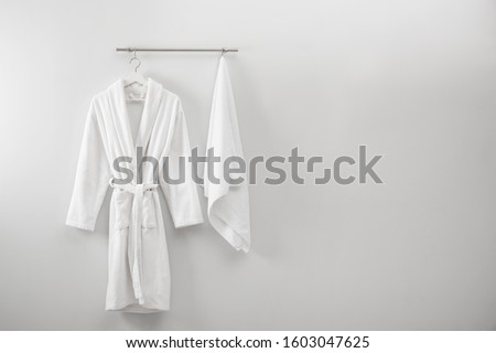 Hanger with clean bathrobe and towel on light wall. Space for text Royalty-Free Stock Photo #1603047625