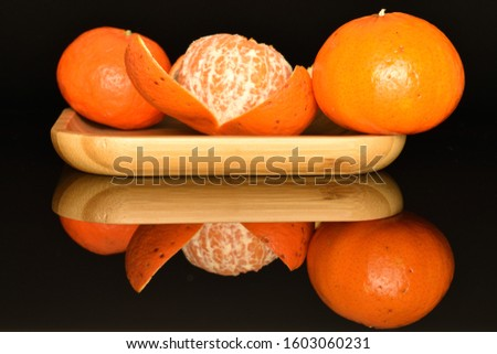 Two whole and one whole, half peeled round bright orange juicy ripe tangerines, lies on a bamboo tray, on a black background. #1603060231