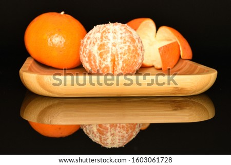One whole and one whole, peeled round bright orange juicy ripe tangerines, lies on a bamboo tray, on a black background. The mandarin peel lies nearby. #1603061728