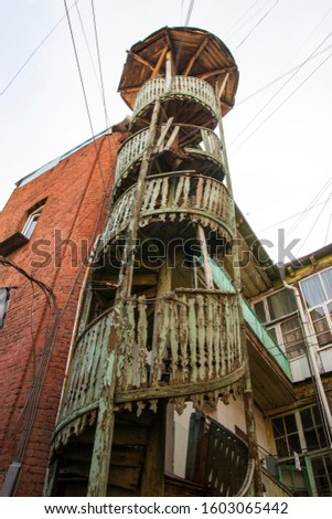 Old Tbilisi. Courtyard in the old town with a broken spiral staircase and lots of clothesline.  #1603065442