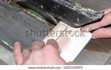 the process of cutting tile on a special tool with a diamond disk and wet sawing without dust. repair work performed by a specialist with a modern tool. #1603106092
