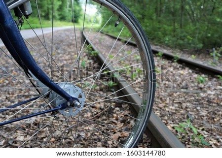Bicycle spokes radiate from  axel of front bike wheel which butts up against metal rail road tracks.  Bushes, leaves, sidewalk in background.   #1603144780