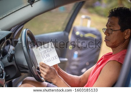 Male asian traveller wearing red shirt, reading glass at Sydney south sitting on driver seat checking reading reviewing bushfire emergency rescue plan white booklet prior leaving the house #1603185133