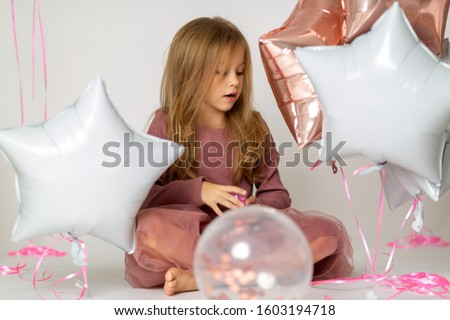 Happy brightful image of cute joyful little girl in tulle skirt sitting on present with balloons isolated on white background. Amazing charming birthday fashionable kid looking to camera