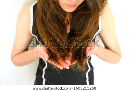 Cropped shot view of woman holding her damaged split ended hair (Focus at ends hair). Hair damage is risk for further damage and breakage. It may also look dull or frizzy and be difficult to manage. #1603213258