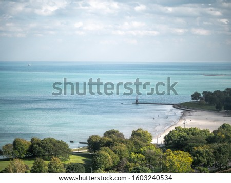 A beautiful aerial view of a beach in Chicago on a sunny summer day with fluffy white clouds in the sky and trees framing the sandy Lake Michigan shoreline below a people wade into the water. #1603240534