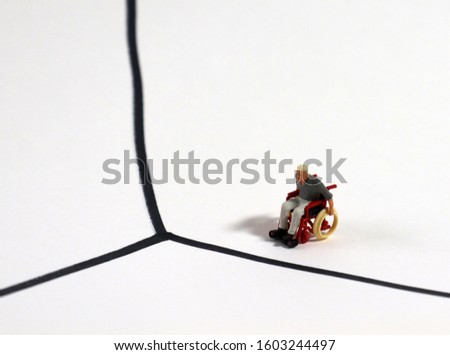 A miniature man in a wheelchair. Concepts on social structural discrimination against the disabled. #1603244497