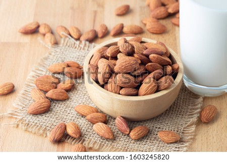 Almond seeds in a bowl wood on the sackcloth And a glass of milk on table wooden background #1603245820