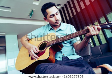 Cheerful guitarist. Cheerful handsome young man playing guitar and smiling while sitting at room, process color #1603277803
