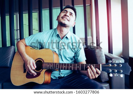 Cheerful guitarist. Cheerful handsome young man playing guitar and smiling while sitting at room, process color #1603277806