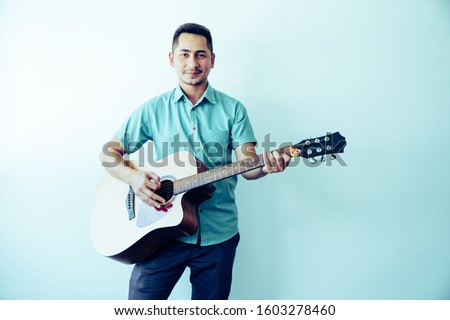 Cheerful guitarist. Cheerful handsome young man playing guitar and smiling while standing on white wall background, Process color. #1603278460