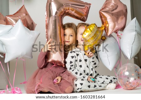 Happy brightful image of cute joyful little girls in tulle skirt sitting on present with balloons isolated on white background. Amazing charming birthday fashionable kid looking to camera