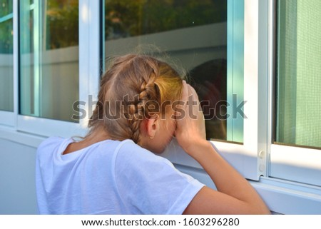 A child looks out the window. Curious little girl looking through the glass. To spy on others. #1603296280