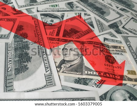 The bright red arrow icon on a background of money. The concept of changing course of US dollar on the market. Devaluation, collapse, stagnation of the economy. #1603379005
