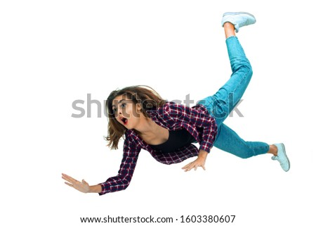 A second before falling. Caucasian young girl falling down in moment with bright emotions and facial expression. Female model in casual clothes. Shocked, scared, screaming. Copyspace for ad. #1603380607