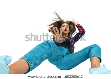 A second before falling. Caucasian young girl falling down in moment with bright emotions and facial expression. Female model in casual clothes. Shocked, scared, screaming. Copyspace for ad. #1603380613