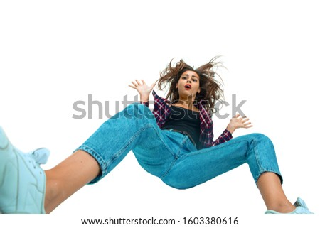A second before falling. Caucasian young girl falling down in moment with bright emotions and facial expression. Female model in casual clothes. Shocked, scared, screaming. Copyspace for ad. #1603380616